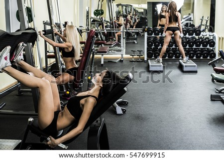 Portrait of three young adult Girls do exercise for legs and hands. in fitness gym on mirror with reflection and window background. 3 woman with long blond and brunette hair sitting smiling face