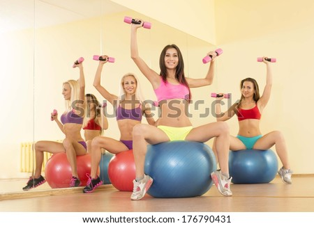 Portrait of Three young adult sexy blond and brunette women Looking At Camera, doing sit-ups on exercise balls in gym on mirror reflection background Sitting on yellow floor - stock photo