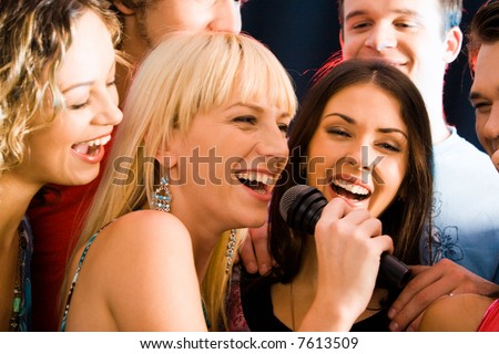 Portrait of three young attractive women singing together - stock photo