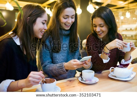 Portrait of three young beautiful women using mobile phone at cafe shop.