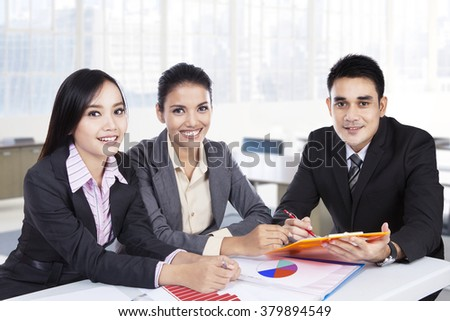 Portrait of three young business team smiling at the camera while sitting in the office and working together - stock photo