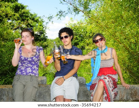 Portrait of three young friends drinking beer in natural environment