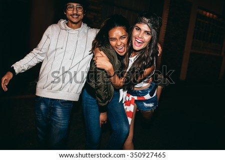 Portrait of three young friends having fun together in outdoor party. Crazy young best friends hanging out. - stock photo