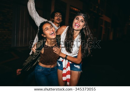 Portrait of three young friends having party outdoors. Cheerful young best friends hanging out at night. - stock photo