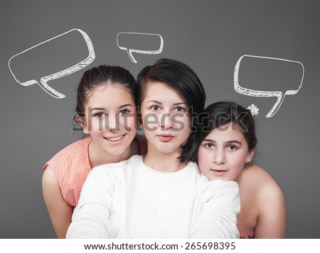 Portrait of three young girls with speech bubbles - stock photo