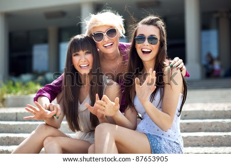 Portrait of three young ladies wearing sunglasses - stock photo