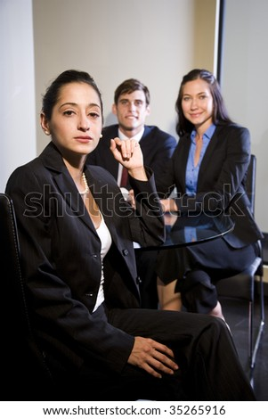 Portrait of three young multi-ethnic businesspeople sitting in office