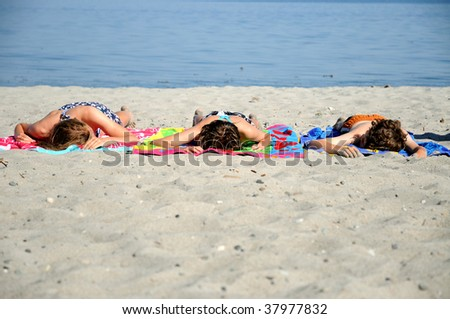 portrait of three young people lying on the beach - stock photo
