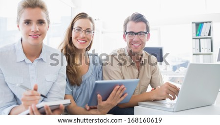 Portrait of three young people working in a bright office