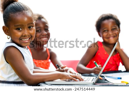 Portrait of threesome African kids with laptop at table.Isolated on white background. - stock photo