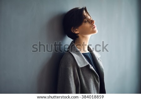 Portrait of tired beautiful woman on dark background - stock photo