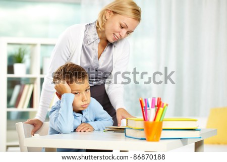 Portrait of tired boy looking at camera while tutor explaining something near by - stock photo