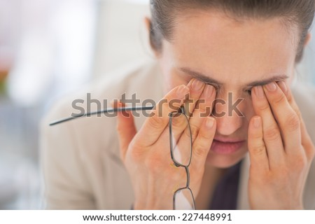 Portrait of tired business woman with eyeglasses in office - stock photo