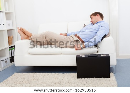 Portrait Of Tired Businessman Sleeping On Couch - stock photo