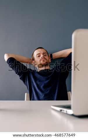 Portrait of tired businessman with arms on head looking at laptop while leaning on grey wall.Copy space