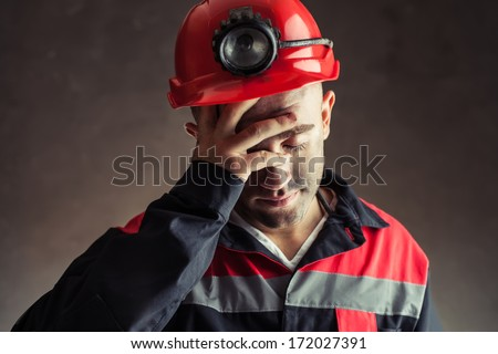 Portrait of tired coal miner holding hand his head against a dark background    - stock photo