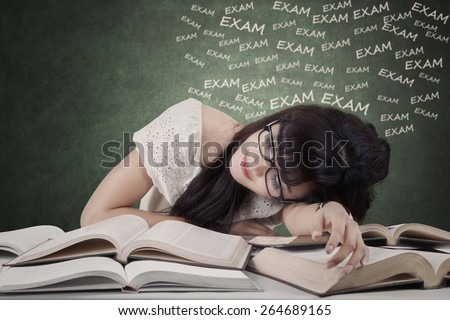 Portrait of tired female student preparing exam and sleep over the textbooks - stock photo