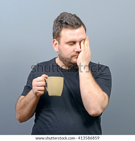 Portrait of tired man having first morning coffee and still speepy - stock photo