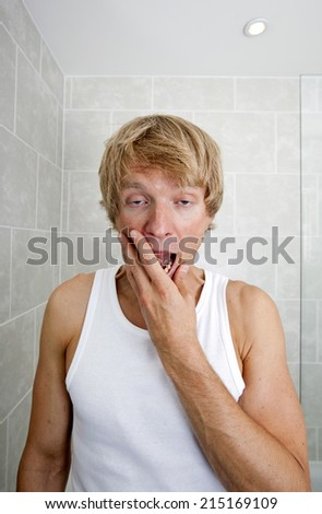 Portrait of tired man yawning in bathroom - stock photo