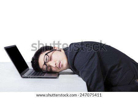 Portrait of tired manager in business suit sleeping on his laptop computer, isolated on white - stock photo