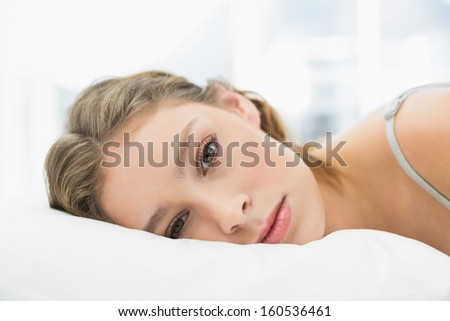Portrait of tired pretty woman lying in her bed in the bedroom looking at camera