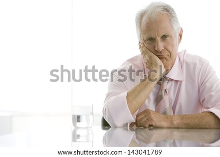 Portrait of tired senior businessman with hand on face at desk - stock photo