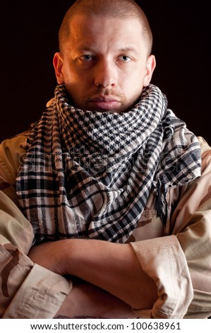 Portrait of tired soldier in camouflage and arabian scarf