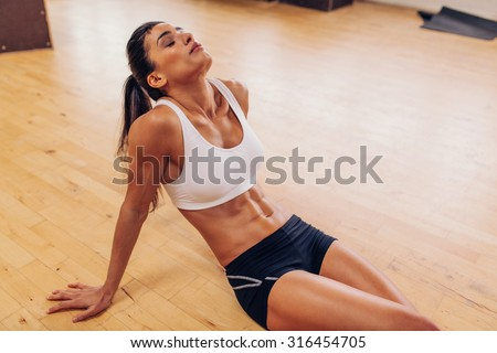 Portrait of tired woman having rest after workout. Tired and exhausted female athlete sitting on floor at gym. - stock photo