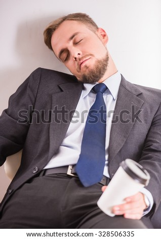 Portrait of tired young businessman drinking coffee on white background - stock photo