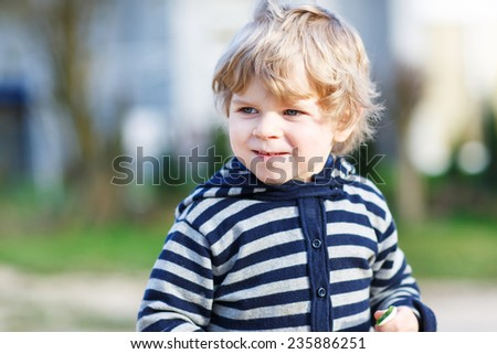 Portrait of toddler boy having fun on outdoor playground. Portrait of little kid with blond hairs and jacket with stripes. - stock photo