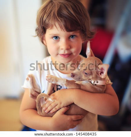 Portrait of toddler girl with baby dog pet. - stock photo