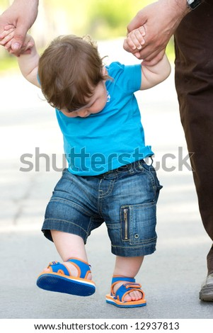 portrait of toddler taking his first steps - stock photo
