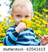 Portrait of toddler with yellow flower in a garden - stock photo