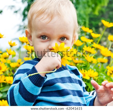 Portrait of toddler with yellow flower in a garden