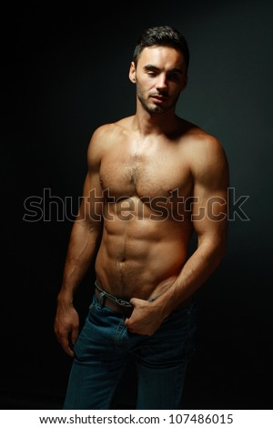 portrait of topless athletic macho man posing over black background