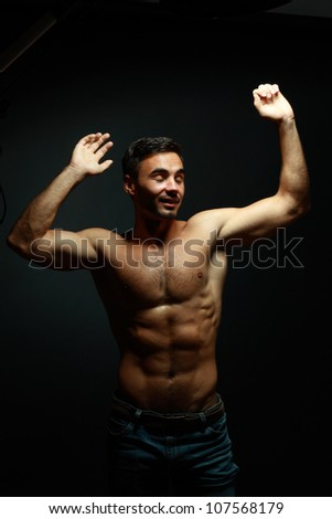 portrait of topless athletic man dancing over black background - stock photo
