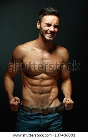 portrait of topless athletic smiling macho man posing with eyes closed and strained
