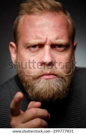 Portrait of tough bearded guy on black background. Short-haired blond man having a bone to pick with someone. - stock photo