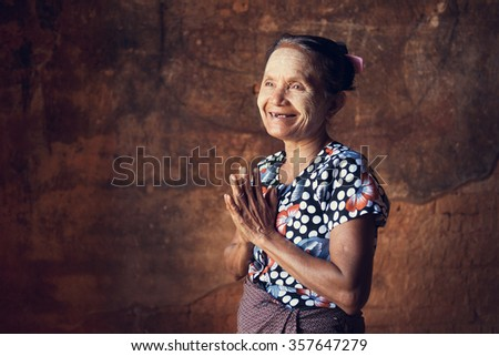 Portrait of traditional Asian Burmese woman greeting, standing inside a temple, low light, Bagan, Myanmar - stock photo