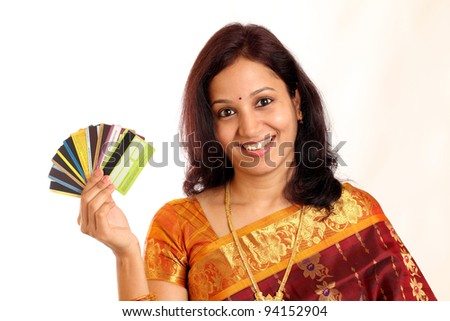 Portrait of traditional happy Indian woman holding credit and debit cards