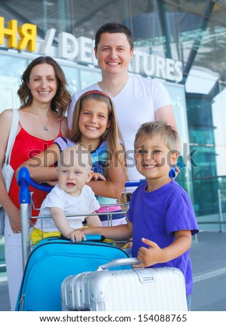Portrait of traveling family of five with suitcases in airport - stock photo