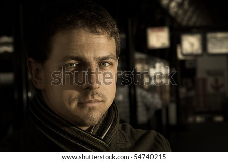 Portrait of traveling man, winter clothes, at train station - stock photo
