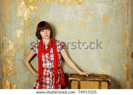 Portrait of traveling woman and her suitcase. Subject standing in front of the old concrete wall