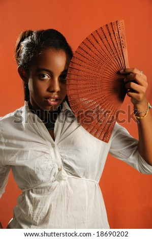 Portrait of trendy african fashion girl with fan - stock photo