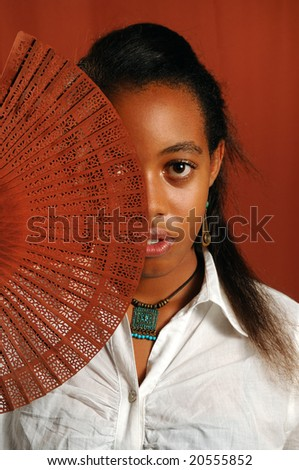 Portrait of trendy african fashion girl with hand fan - stock photo
