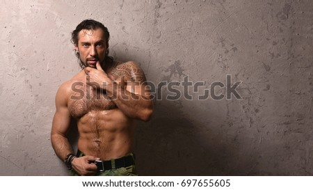 Portrait of trendy athletic man against concrete wall