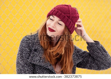 Portrait of Trendy Beauty Girl Standing at the Yellow Wall Background. Urban Fashion Concept  With Red Hat and Red Lips. The Gray Coat Perfect Makeup. Spring Color. Chic Long Hair. Smiling. - stock photo