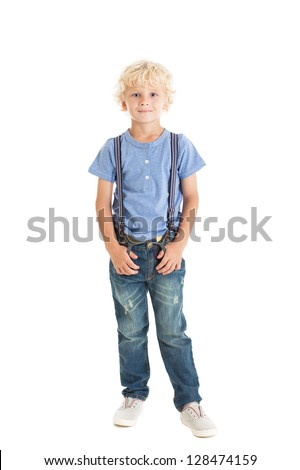 Portrait of trendy cute curly blond boy wearing a blue shirt, suspenders, jeans and sneakers. Studio shot, isolated on white background. - stock photo