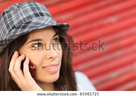 Portrait of trendy girl leaning on red background - stock photo