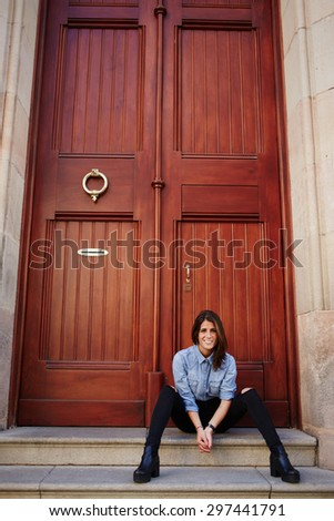 Portrait of trendy glamorous woman in stylish clothing sitting on the stairs in urban setting against vintage style door with copy space for your text message, smiling hipster girl looking at camera - stock photo